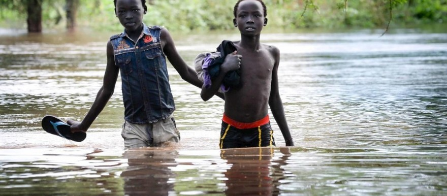 Two boys pick their way along a flooded road in Maban county, South Sudan. Photo: UNHCR/Elizabeth Stuart