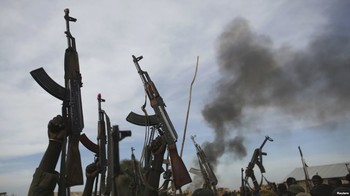 File photo: Rebel fighters hold up their rifles as they walk in front of a bushfire in a rebel-controlled territory in Upper Nile state, South Sudan Feb. 13, 2014.