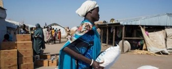 Photo: South Sudanese mother carries a bag of cereals provided by the WFP in in El Alagaya refugee camp in White Nile state (Ala Kheir/WFP)