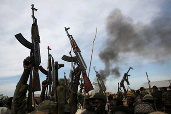 File photo: Rebel fighters hold up their rifles as they walk in front of a bushfire in a rebel-controlled territory in Upper Nile State in 2014. (REUTERS)