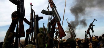 Photo: Rebel fighters hold up their rifles as they walk in front of a bushfire in a rebel-controlled territory in Upper Nile state, South Sudan Feb. 13, 2014.(Reuters)