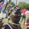 File photo: A South Sudanese woman wears the national flag and carries a mock gun as she attends an Independence Day ceremony in Juba, July 9, 2015. (VOA)